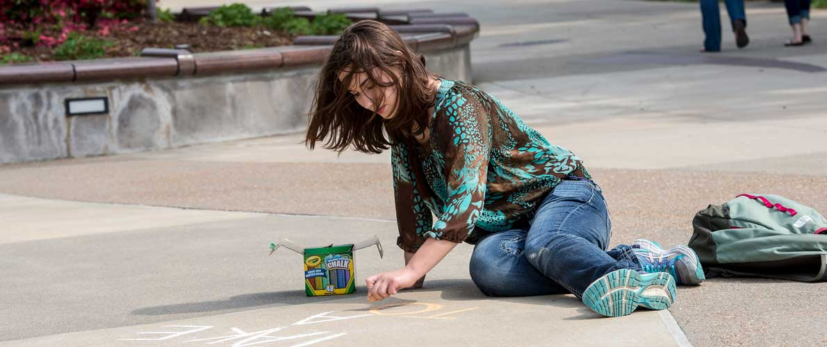 student drawing on campus sidewalk with calk